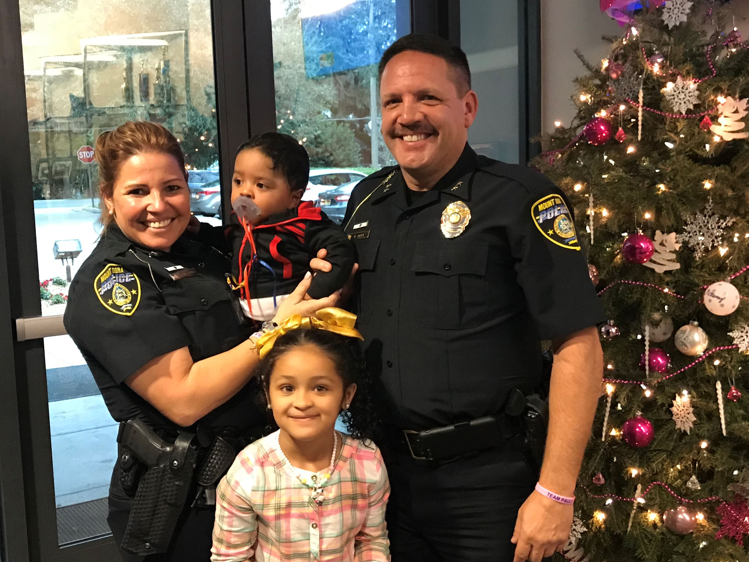 Officer Severance and Deputy Chief Bell with family getting presents